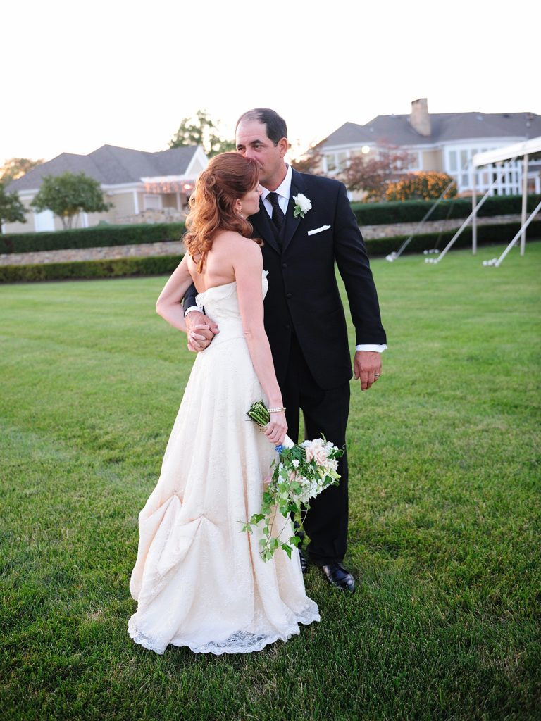 Wedding couple kissing on lawn on private estate taken by NYC Wedding Photographer Wendy G