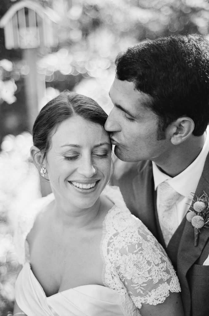 black and white photo of groom kissing bride's face