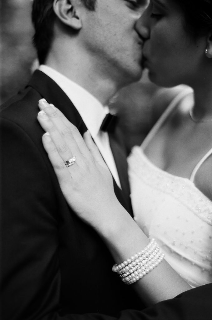 black and white photo of wedding couple kissing in park