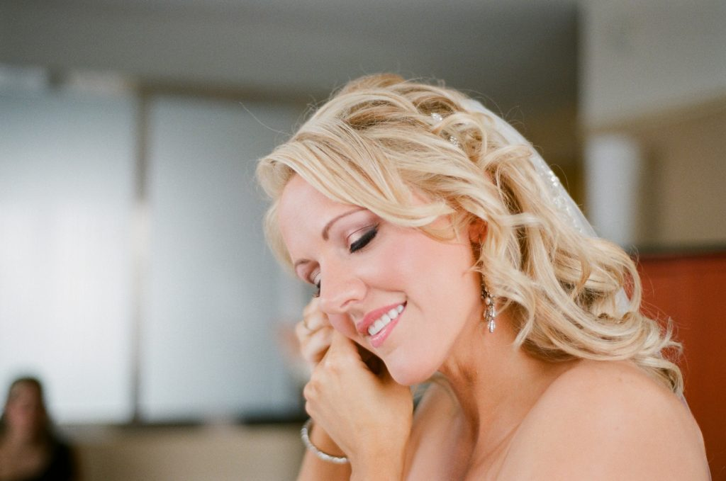 photos of bride putting on her earrings